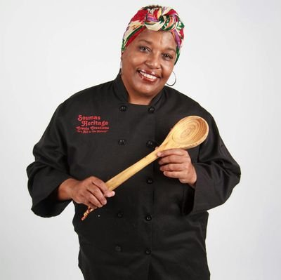 Business owner and cookbook author, Panderina Soumas, holds a wooden spoon.
