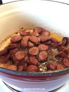 Cast iron pot of sliced smoked sausage being cooked