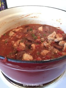 A cast iron pot filled with chicken, smoked sausage, onions, bell peppers, celery, and tomato sauce.