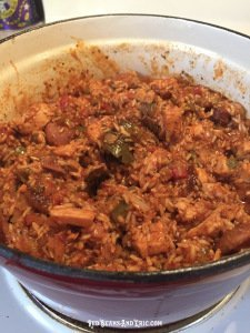 Jambalaya that has cooked in a red cast iron pot on the stove.