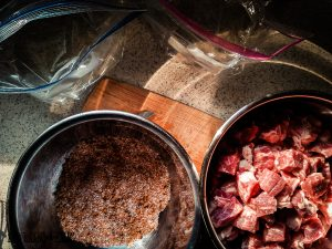 Adding rub to pickled pork and placing them in two different bags