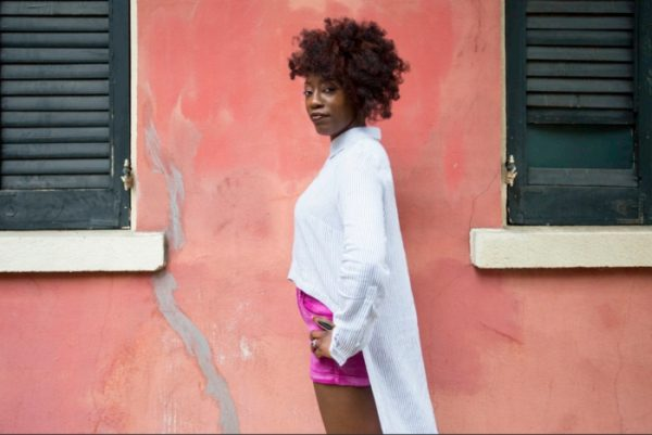 New Orleans Musician, Erica Falls standing outside by a pink wall