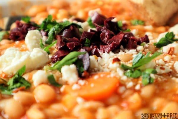 Greek White Bean Soup garnished with Kalamata olives, feta cheese, and fresh chopped parsley.