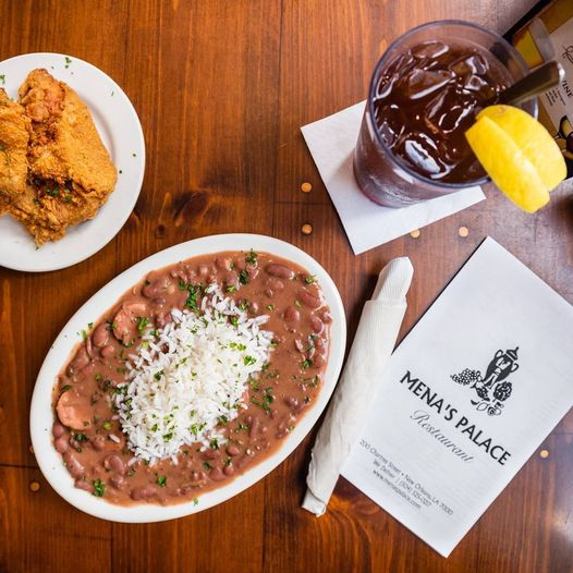 A bowl of red beans and rice with fried chicken and a glass of iced tea from Mena's Palace restaurant in New Orleans