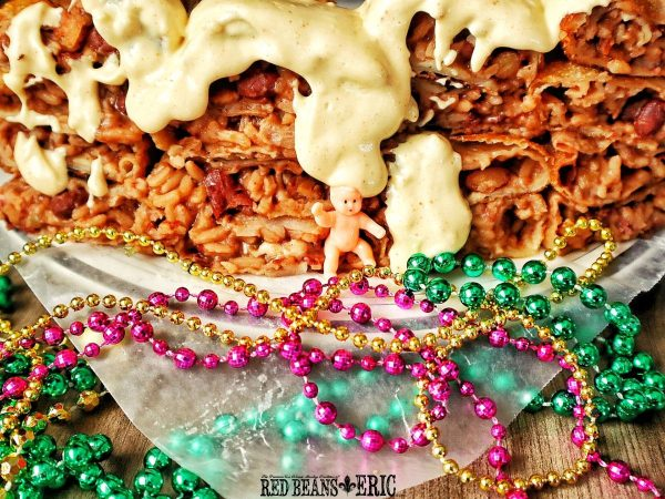 A wall of cut in half Red Beans and Rice Wrapped Egg Rolls with dipping sauce dripping onto King Cake Baby.