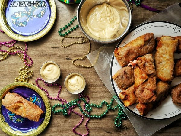 Spread of Red Beans and Rice Wrapped Egg Rolls, dipping sauce, and Mardi Gras beads