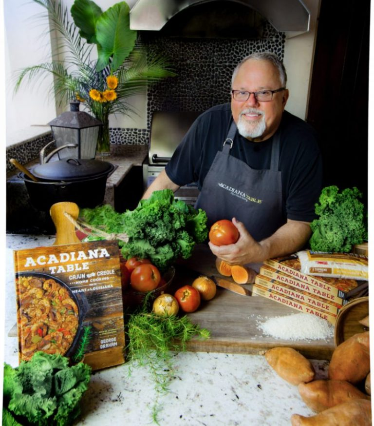 Cookbook author and food blogger George Graham stands at a table with his cookbook, Acadiana Table.