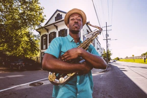 Musician Calvin Johnson holding his saxophone with a house behind him