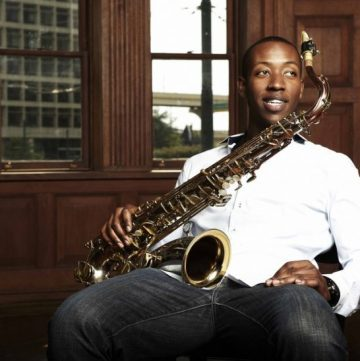 Musician Calvin Johnson sits in a chair with his saxophone on his lap