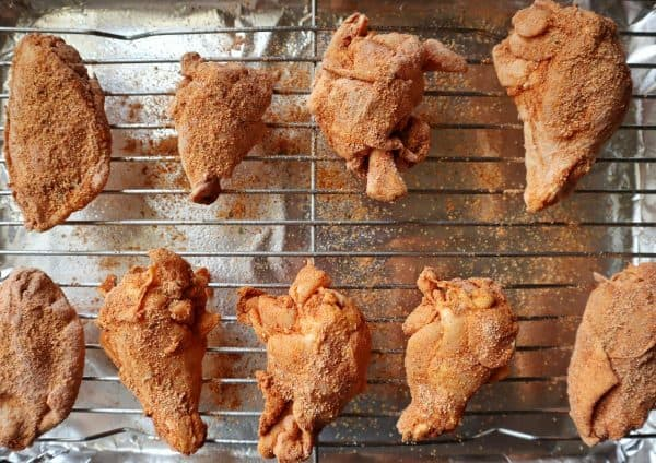 Chicken wings dredged in a flour mixture and sitting on a wire rack waiting to be baked to a crisp.
