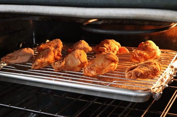 Chicken wings on a wire rack and baking sheet and in the oven baking.