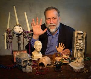 Author Michael Murphy sitting at a table with skulls and candles promoting his book Fear Dat in 2015